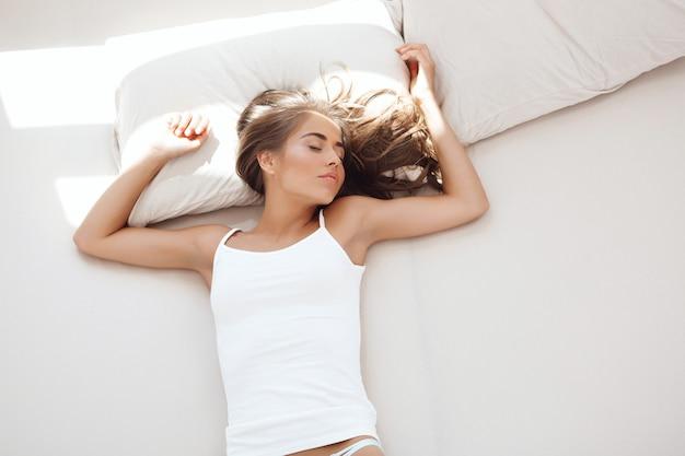 Mujer hermosa joven que duerme en cama temprano en la mañana. disparo desde arriba ...