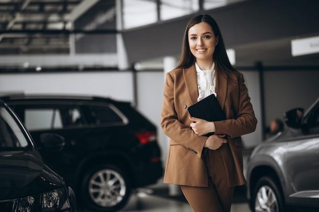 Mujer hermosa joven que elige el coche en una sala de exposición de automóviles