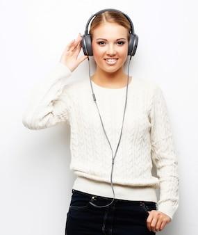 Mujer hermosa joven que escucha la música de los auriculares
