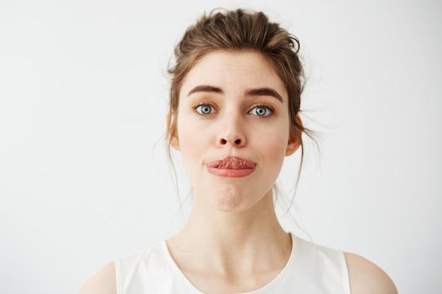 Mujer hermosa joven que estira la lengua a la nariz.