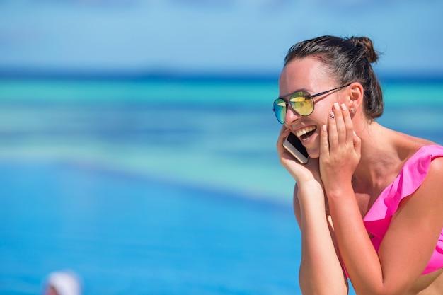 Mujer hermosa joven que habla por teléfono en la playa blanca