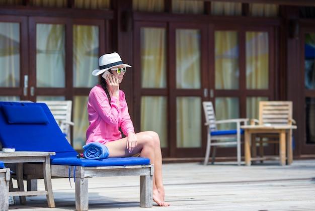 Mujer hermosa joven que habla por teléfono en el resort tropical
