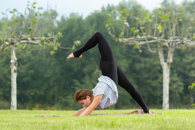 Mujer hermosa joven que hace ejercicio de yoga en el parque verde cerca del estanque