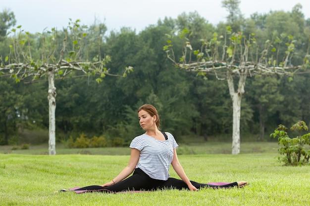 Mujer hermosa joven que hace ejercicio de yoga en el parque verde. concepto de fitness y estilo de vida saludable.