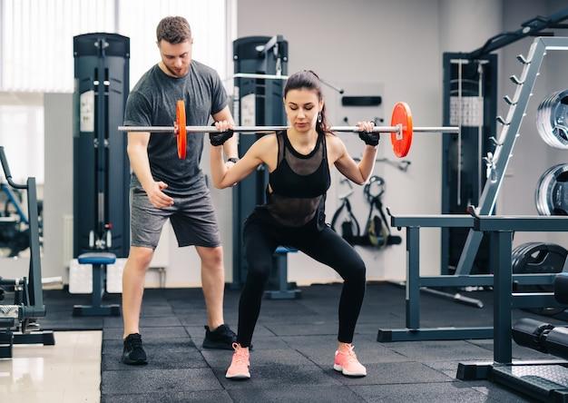 Mujer hermosa joven que hace ejercicios con entrenador personal.