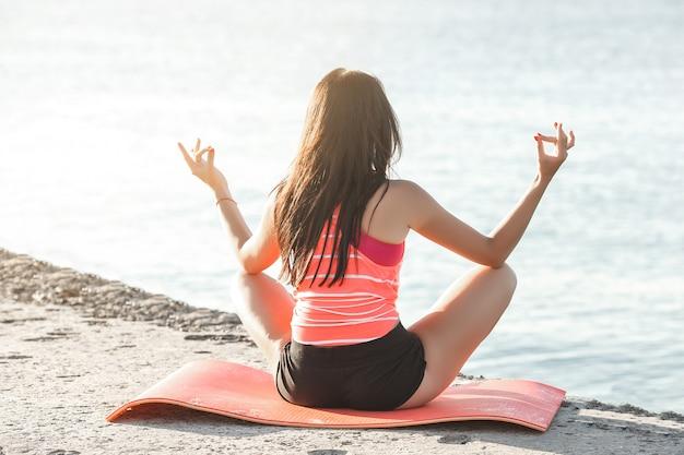Mujer hermosa joven que hace ejercicios de yoga en la playa