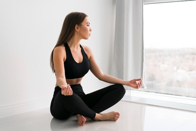 Mujer hermosa joven que hace yoga en el interior