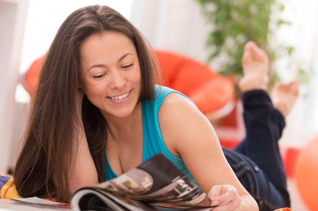 Mujer hermosa joven que lee en casa