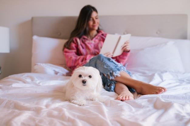 Mujer hermosa joven que lee un libro en cama en casa. lindo perro maltés además