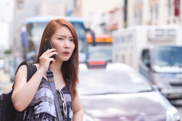 Mujer hermosa joven que llama el taxi público por el teléfono en singapur. de pie junto a la carretera