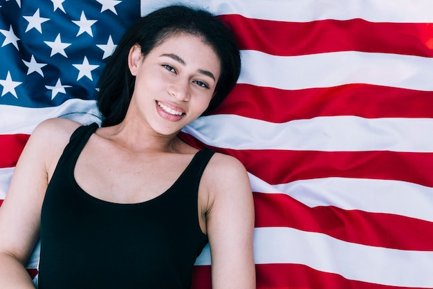 Mujer hermosa joven que miente en bandera americana
