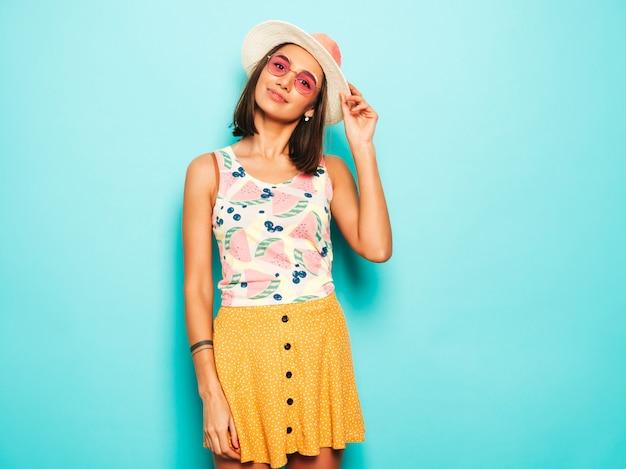 Mujer hermosa joven que mira la cámara en sombrero. chica de moda en verano casual camiseta blanca y falda amarilla en gafas de sol redondas. la hembra positiva muestra emociones faciales. modelo divertido aislado en azul