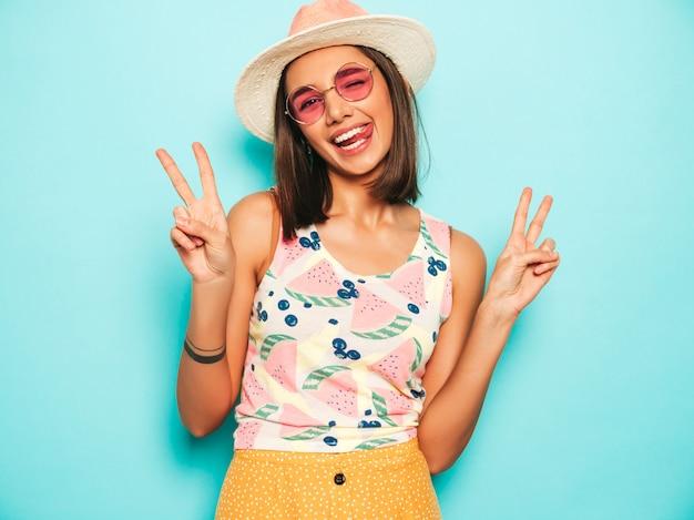 Mujer hermosa joven que mira la cámara en sombrero. chica de moda en verano casual camiseta blanca y falda amarilla en gafas de sol redondas. la hembra positiva muestra emociones faciales. muestra signo de paz