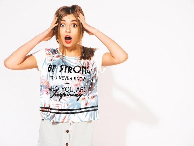 Mujer hermosa joven que mira. muchacha de moda en ropa casual del verano. modelo sorprendida y sorprendida sosteniendo su cabeza