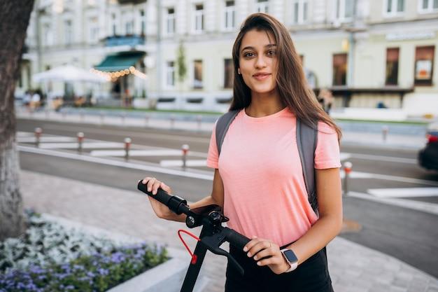 Mujer hermosa joven que monta un scooter eléctrico.