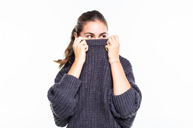 Mujer hermosa joven que oculta la cara en suéter rojo soñador mirando en la cámara sobre la pared blanca