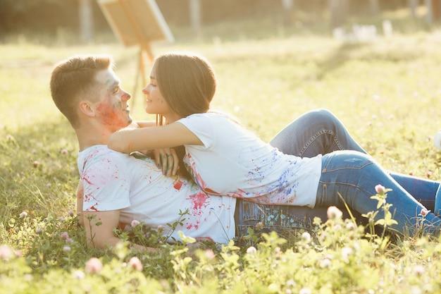 Mujer hermosa joven que pone en su novio que lleva la camiseta coloreada. pareja bastante alegre sonriendo el uno al otro