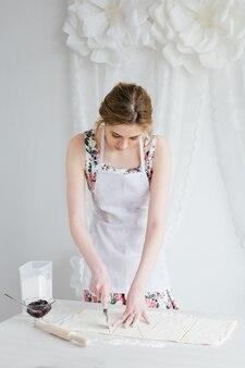Mujer hermosa joven que prepara los cruasanes caseros