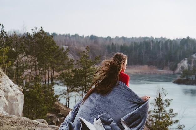 Mujer hermosa joven que presenta en un lago