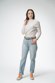 Mujer hermosa joven que presenta en pantalones vaqueros en el fondo blanco