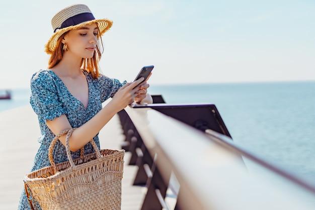 Mujer hermosa joven que se queda en el muelle y navegar por el teléfono inteligente en un día soleado vistiendo ropa de moda ...