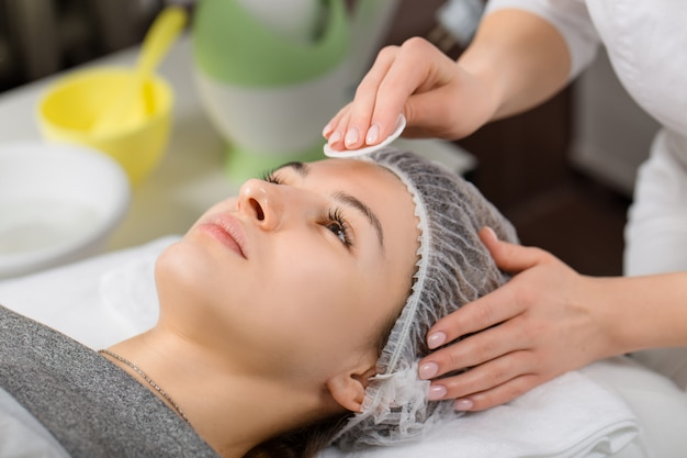 Mujer hermosa joven que recibe masaje facial