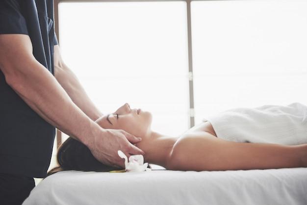 Mujer hermosa joven que se relaja de la cara del masaje