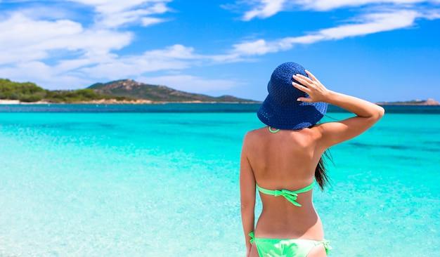 Mujer hermosa joven que se relaja en la playa tropical de arena blanca
