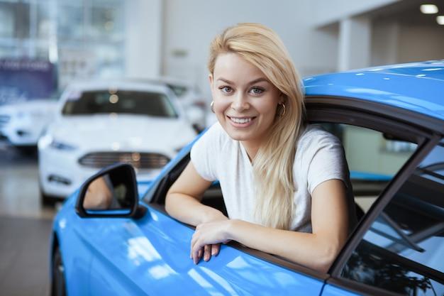 Mujer hermosa joven que sonríe a la cámara que elige un coche nuevo para comprar en el salón del concesionario local