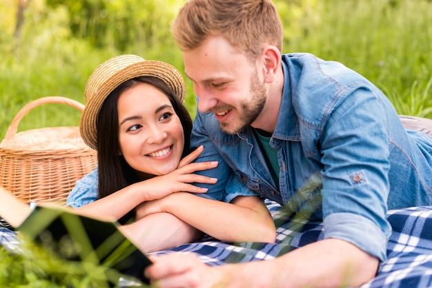 Mujer hermosa joven que sonríe en el hombre de la lectura en campo