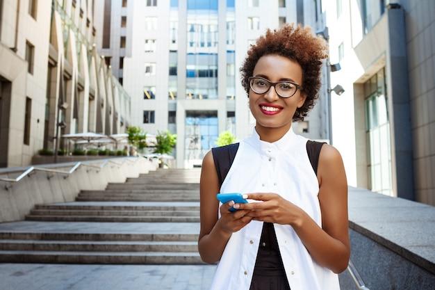 Mujer hermosa joven que sonríe sosteniendo el teléfono caminando por la ciudad