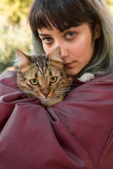 Mujer hermosa joven que sostiene el gato de gato atigrado