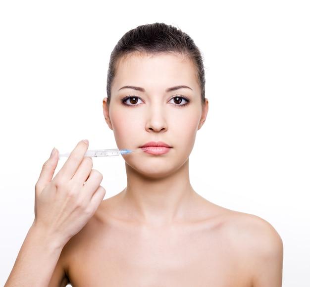 Mujer hermosa joven que sostiene la jeringa médica cerca de los labios