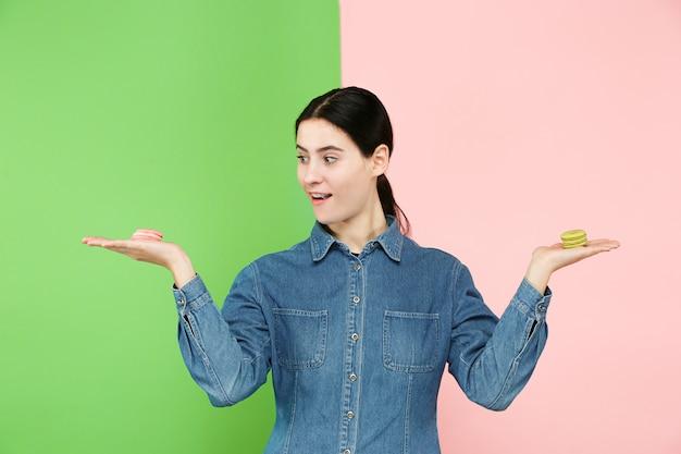Mujer hermosa joven que sostiene los pasteles de los macarrones en sus manos, sobre coloreado de moda en el estudio.
