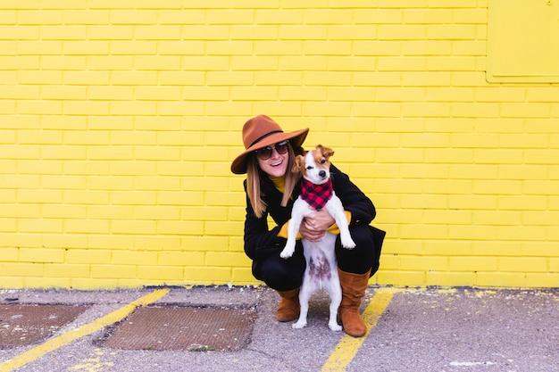Mujer hermosa joven que sostiene y que ama a su perro. pared de ladrillo amarillo. amor y mascotas al aire libre