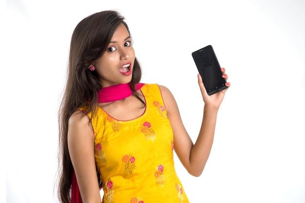 Mujer hermosa joven que sostiene y que muestra la pantalla en blanco del teléfono inteligente o teléfono móvil o tableta en un blanco