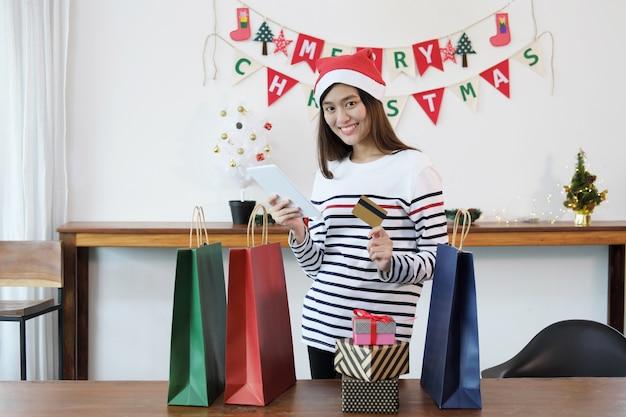Mujer hermosa joven que sostiene la tableta digital y la tarjeta de crédito con muchos bolsos de compras y de la caja de regalo de la navidad.
