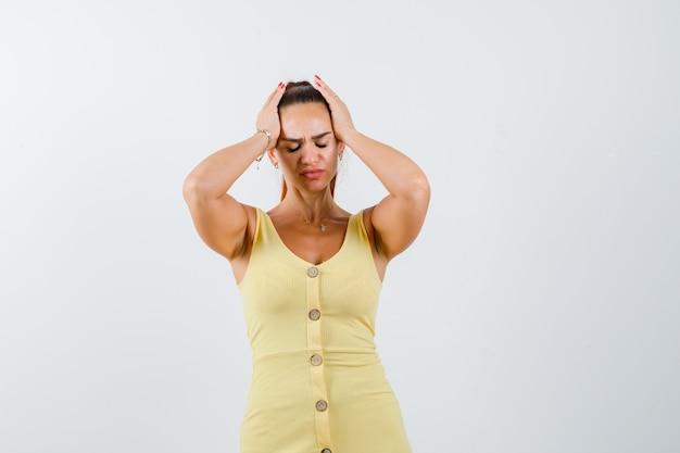 Mujer hermosa joven que sufre de dolor de cabeza en el vestido y parece doloroso. vista frontal.
