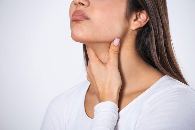 Mujer hermosa joven que sufre de dolor en la garganta, tocando la zona inflamada en su cuello, espacio recortado, vacío, dolor de garganta