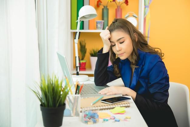 Mujer hermosa joven que tiene dolor de cabeza que trabaja en la computadora en casa