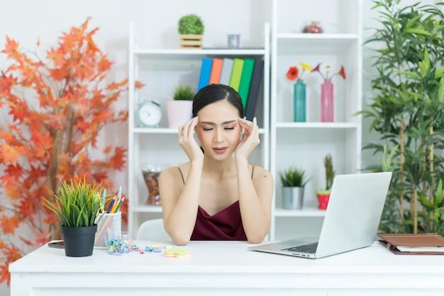 Mujer hermosa joven que tiene dolor de cabeza que trabaja en el ordenador en casa