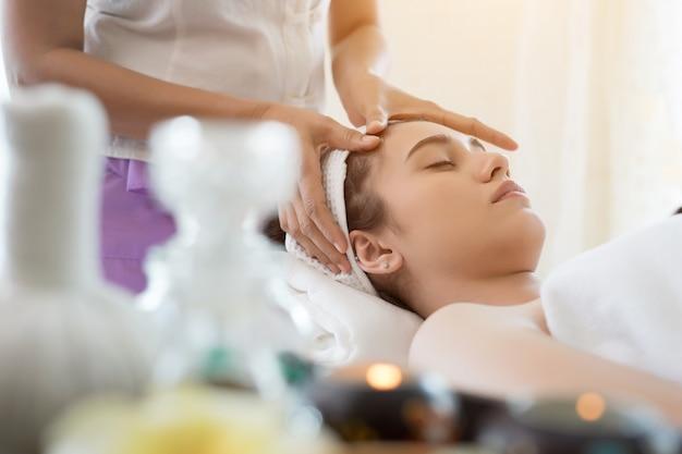 Mujer hermosa joven que tiene masaje facial que se relaja en balneario.