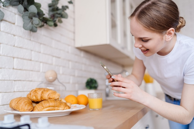 Mujer hermosa joven que toma la foto en el teléfono móvil de croissants