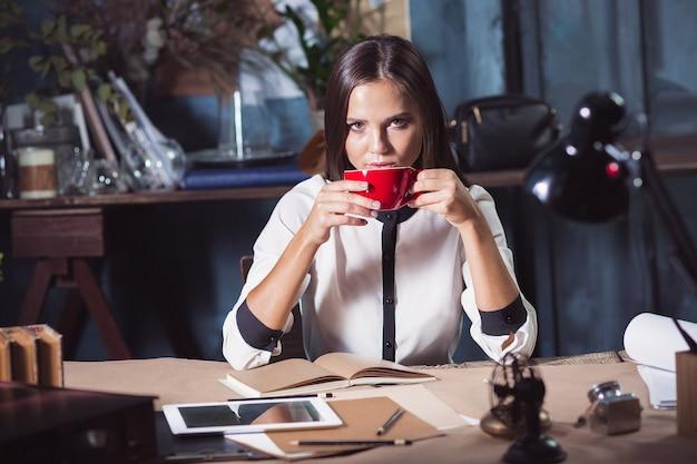 Mujer hermosa joven que trabaja con una taza de café y un cuaderno en la oficina del desván