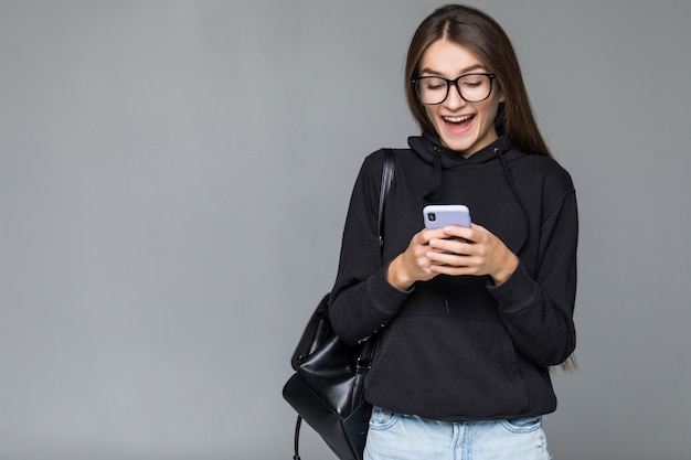 Mujer hermosa joven que usa el teléfono inteligente aislado en la pared gris