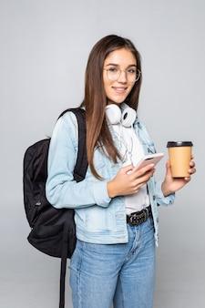 Mujer hermosa joven que usa el teléfono inteligente con café aislado en la pared blanca