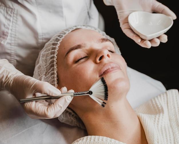Mujer hermosa joven recibiendo un tratamiento para la piel de la cara en el spa