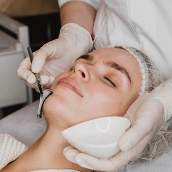Mujer hermosa joven recibiendo un tratamiento para la piel de la cara