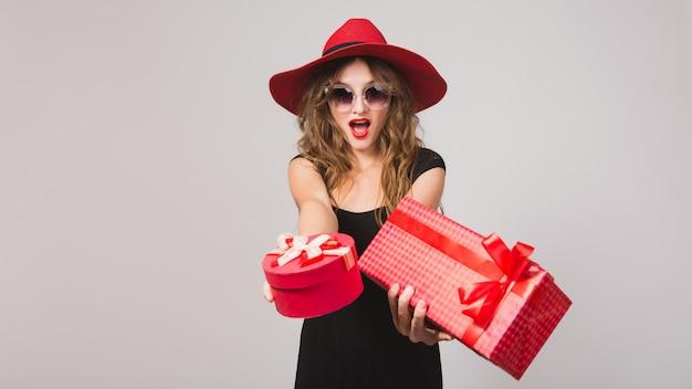 Mujer hermosa joven con regalos, vestido negro, sombrero rojo, gafas de sol, feliz, sonriente, sexy, elegante, cajas de regalo, celebrando, positivo, emocional