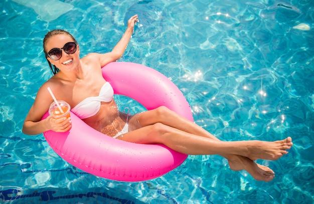 La mujer hermosa joven se está relajando en piscina.